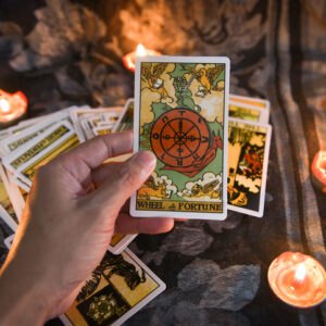 Hand holding tarot card with candlelight on the darkness background for Astrology Occult Magic illustration / Magic Spiritual Horoscopes and Palm reading fortune teller concept