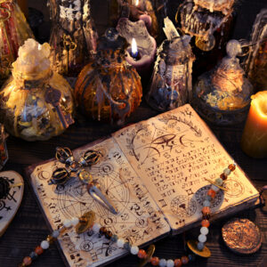 Ancient witch book with magic spell, black candles and decorated bottles. Halloween, esoteric and occult background. No foreign text, all symbols on pages are fictional.